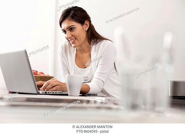 Singapore, Young woman using laptop in kitchen