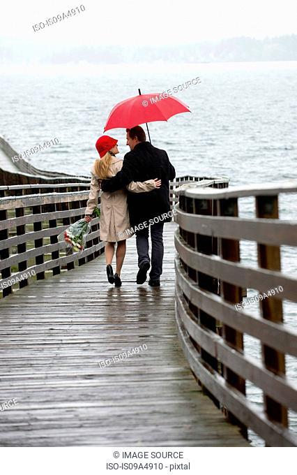 Couple walking on wooden pier in rain
