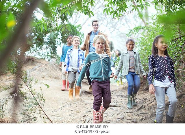 Students and teacher walking in forest