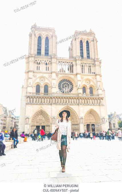 Stylish young woman in front of Notre Dame, Paris, France