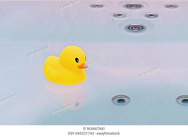 Large yellow rubber duck floating in bathtub jacuzzi. Bath time concept