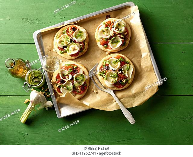 Mini pizzas with rocket, tomatoes and goat's cheese