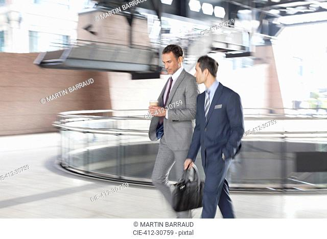 Corporate businessmen with coffee walking and talking