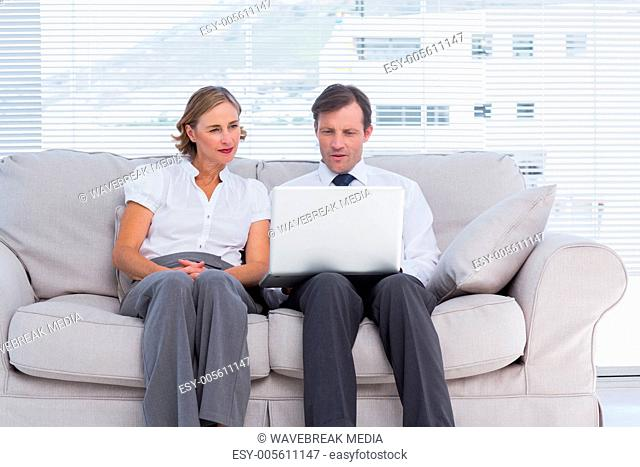 Business people sitting on couch and using laptop