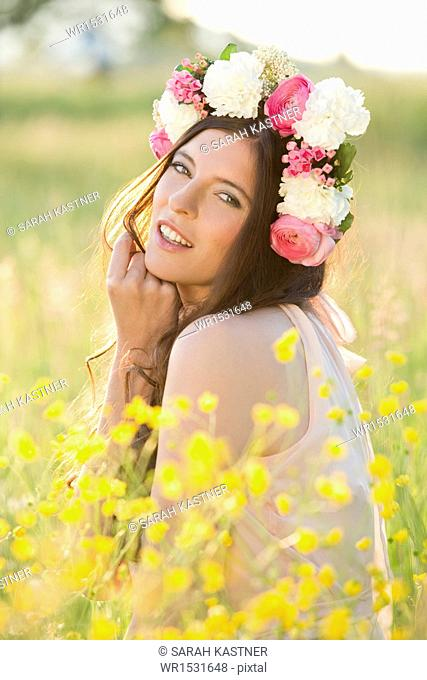 Woman with flower wreath on a meadow
