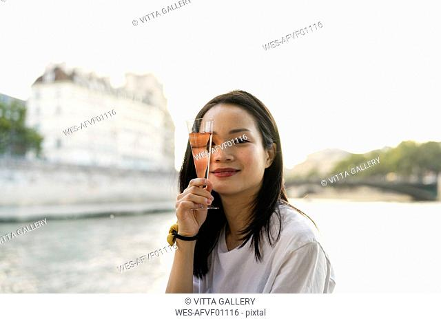 France, Paris, portrait of young woman with champagne glass at river Seine