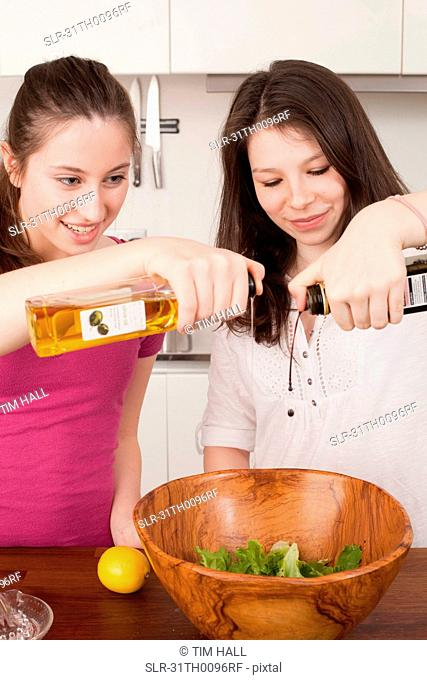 teenage girls preparing salad in kitchen