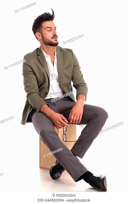 69aa62abae84 proud seated man wearing elegant green suit looks to side while holding  glasses with both hands