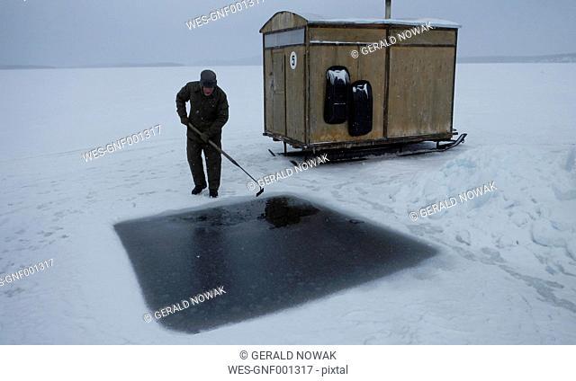 Russia, Arctic Circle Dive Centre, polar circle, White Sea, man preparing hole for ice diving