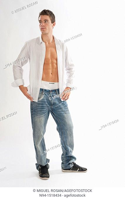 Full-body photograph of a teenage boy in jeans and white shirt open