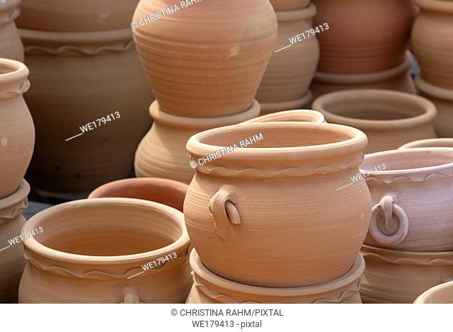 Rustic terracotta pots piled up on display closeup full frame