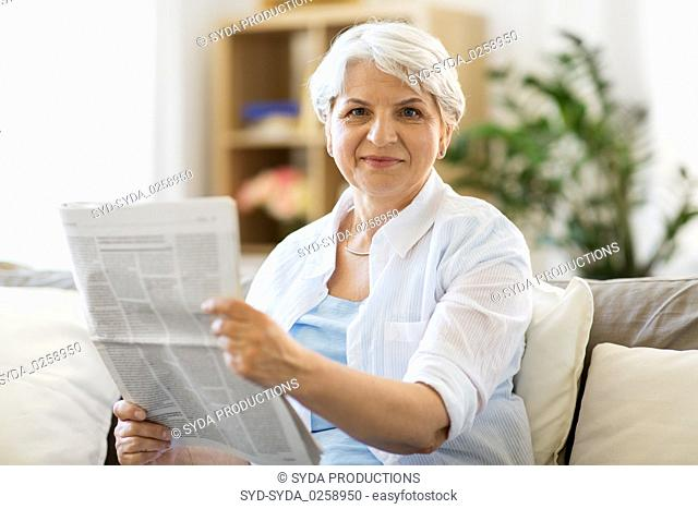senior woman reading newspaper at home