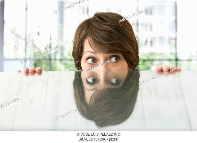 Afraid Caucasian businesswoman hiding behind desk