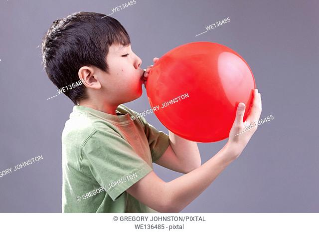 A young boy blows up a red baloon