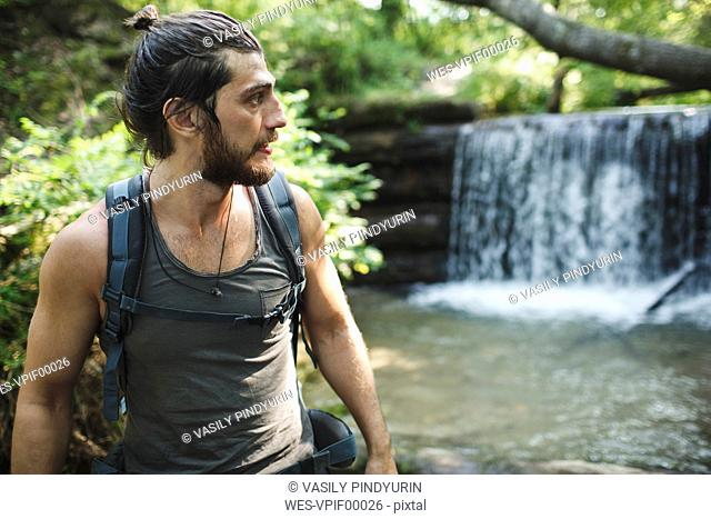 Young man on a hiking trip at a waterfall
