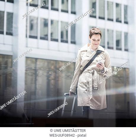 USA, New York City, businesswoman in Manhattan on the go with cell phone