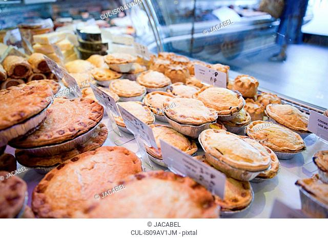 Variety of fresh meat pies in refrigerator at butchers shop