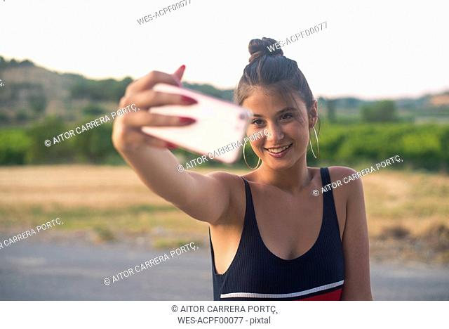 Portrait of smiling teenage girl taking selfie with smartphone outdoors