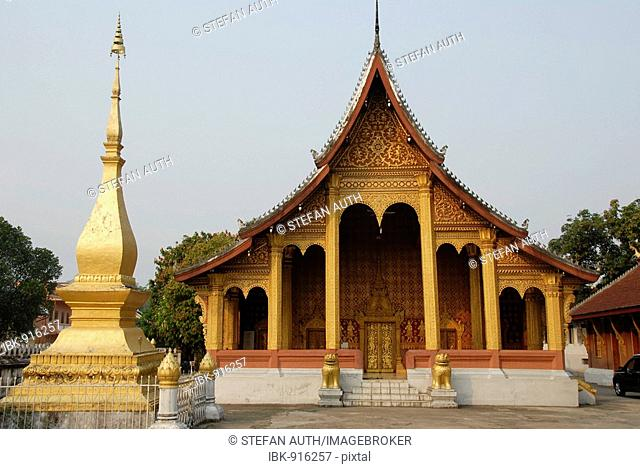 Buddhist Temple in gold and dark red next to a small gold stupa, Wat Sensukarahm, Luang Prabang, Laos, Southeast Asia