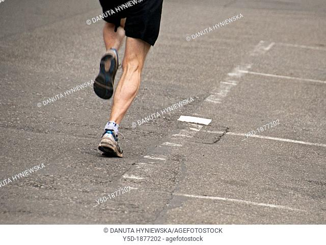 one man jogging on the street, legs only, Geneva, Switzerland