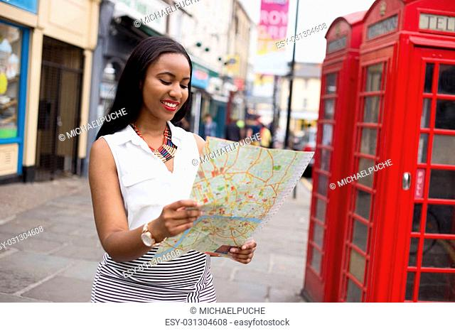 young tourist visiting London reading a map