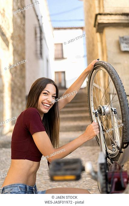 Spain, Baeza, portrait of laughing young woman repairing her bicycle with wrench
