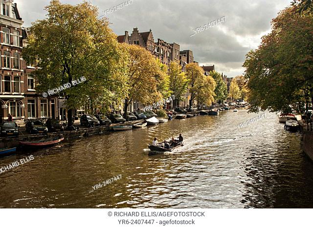 A small boat on the Prinsengracht canal in Jordaan during autumn in Amsterdam