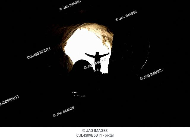 Silhouette of woman with arm raised in cave, Bruniquel, France