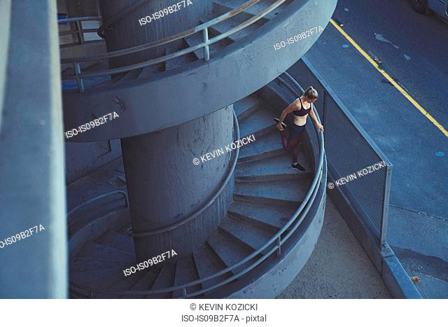 Young woman stretching on spiral staircase outdoors