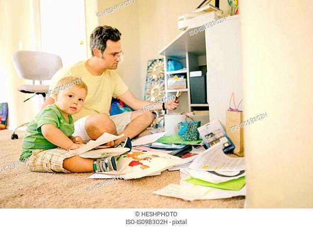 Father and young son sitting on floor creating artwork