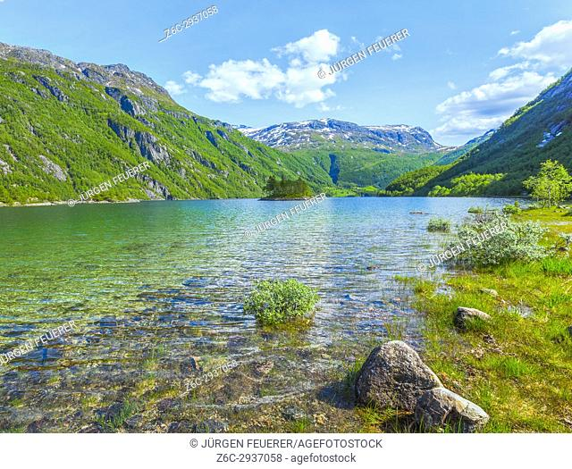 Lake Roldalsvatnet in Norway, with small island and view to village Boten and snow capped mountains, Roldal in Norway, Scandinavia