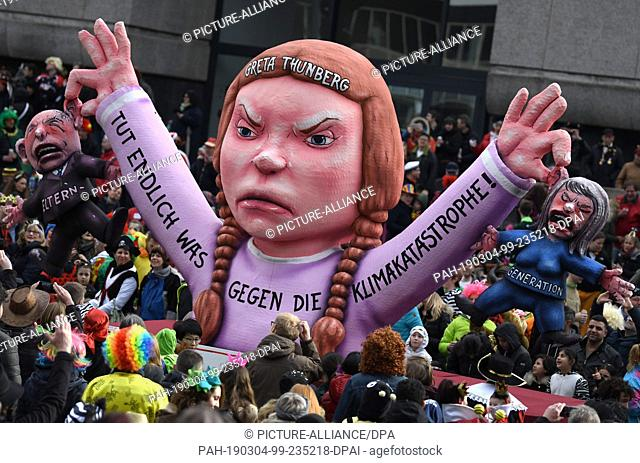 04 March 2019, North Rhine-Westphalia, Düsseldorf: A political theme car with the figure of the Swedish climate activist Greta Thunberg drives the Shrove Monday...