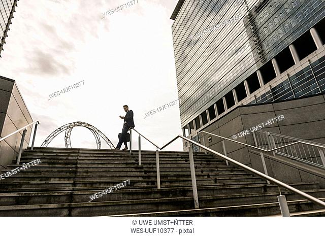 Businessman leaning on railing on top of stairs reading messages