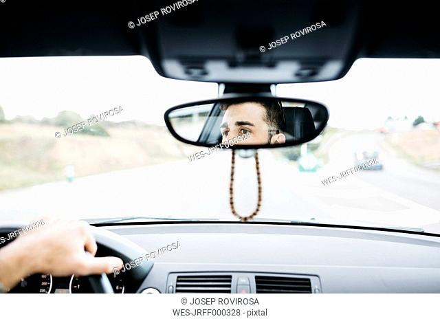 Young man driving a car, close up of rear mirror
