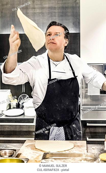 Chef throwing pizza dough mid air in commercial kitchen