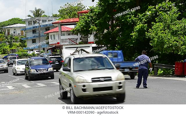 Pohnpei Micronesia Kolonia main town traffic policeman directing traffic at intersection with cars driving by