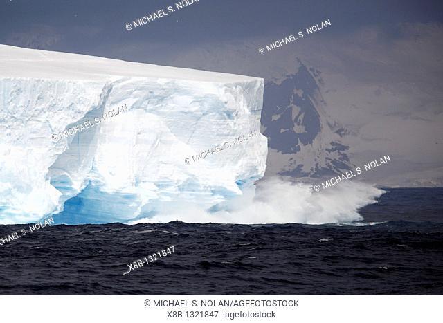 Waves break on the face of a huge tabular iceberg off the coast of Elephant Island near the Antarctic Peninsula
