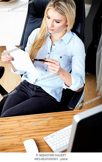 Blond woman sitting at desk checking documents