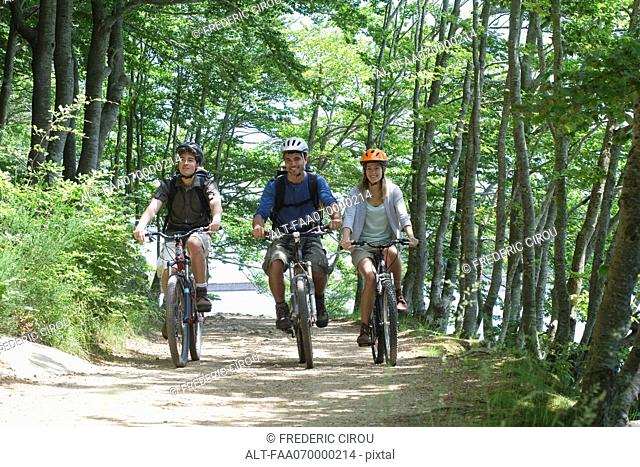 Friends riding bicycles side by side through woods