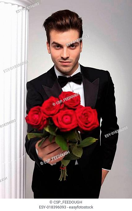 business man giving you a bouquet of red roses