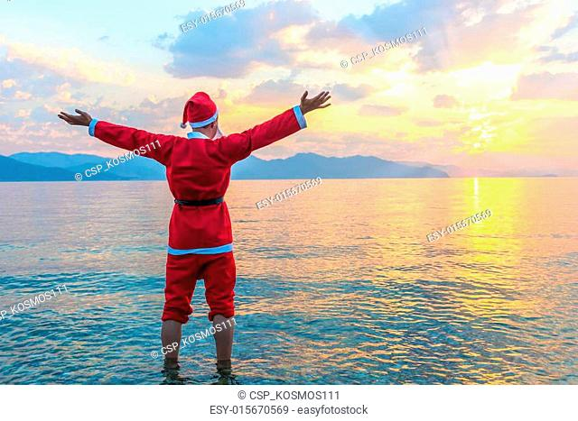 Santa Claus standing barefoot in the sea