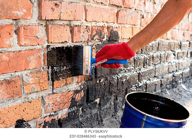 Roofer covered brick wall, bitumen primer for improving adhesion during surfacing, contiguity with rolled waterproofing, during the installation of flat roof