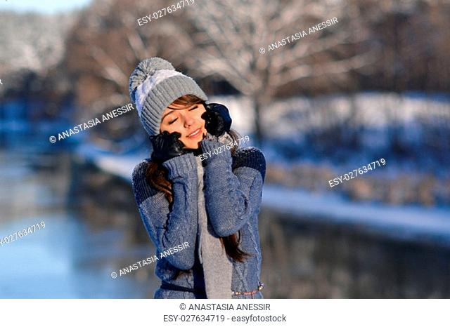Outdoor close up portrait of young beautiful happy smiling girl, wearing stylish knitted winter hat and gloves. Model expressing joy and looking at camera