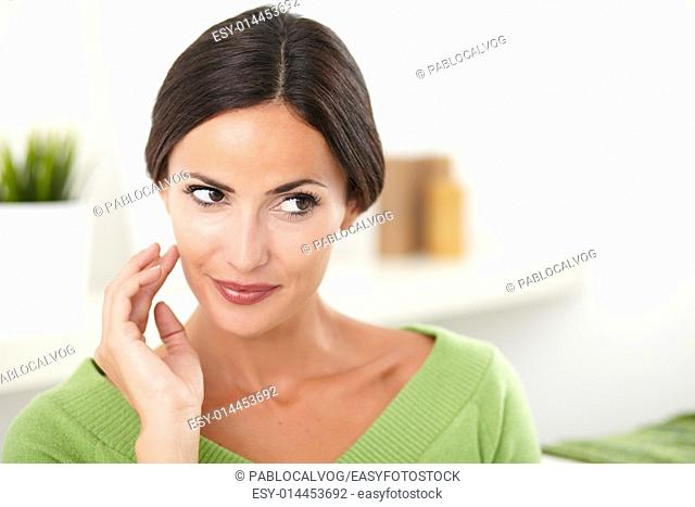 Young confident caucasian woman with hand on face looking away at indoors - copy space