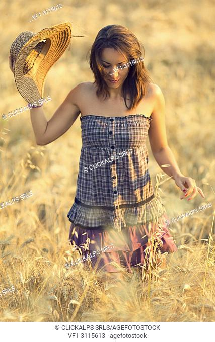 Brunette woman in purple dress in a wheat field at sunset, marche, Italy