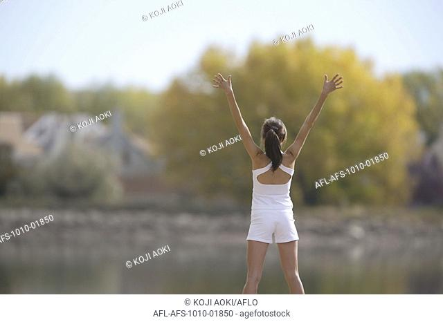 Woman stretching by body of water