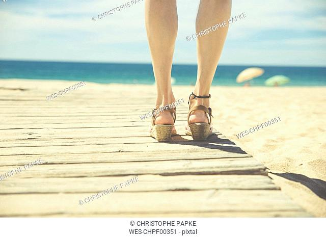 Legs of woman standing at boardwalk on the beach