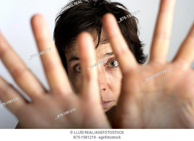 Woman covering camera with her hands