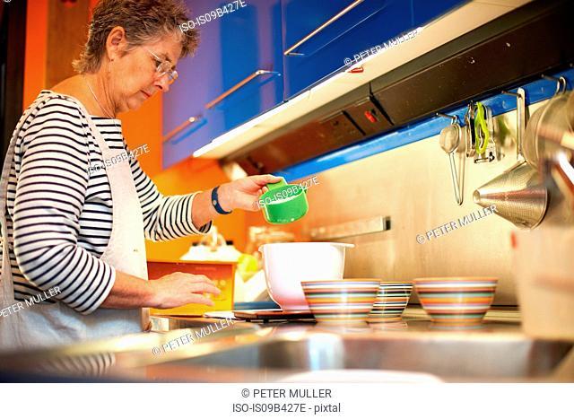 Senior woman in kitchen, measuring ingredients into mixing bowl