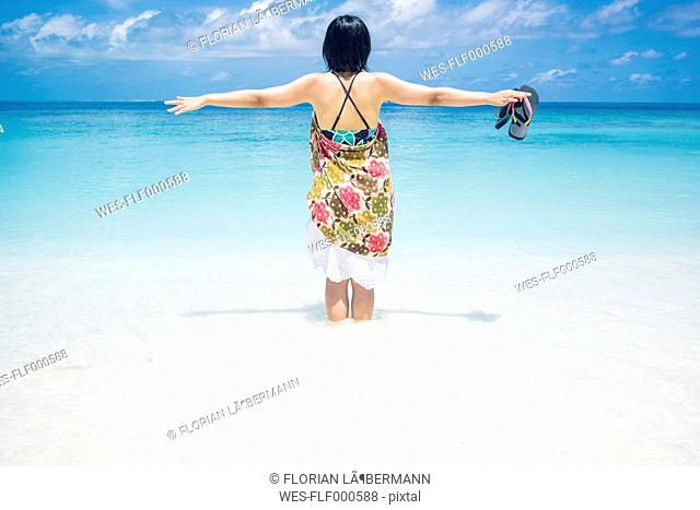 Maledives, Ari Atoll, young woman standing in water at seafront